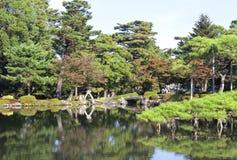 由一个湖的秋天庭院有五颜六色的树的,杉树 免版税图库摄影