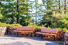 由一个石墙的公园长椅在公园 免版税库存照片