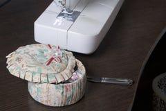 由一位单独企业家的缝合的衣裳 一台缝纫机、一个小箱有辅助部件的和其他工具在桌面上说谎 库存图片