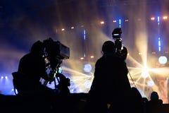 由一位摄影师的电视广播在音乐会期间 与操作员的照相机在高平台 图库摄影