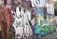 由一位未知的艺术家的五颜六色的街道艺术在一个大厦的墙壁上在Fitzroy胡同的 免版税库存图片