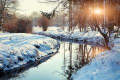由一条河的冬天风景在日落期间 库存照片