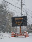 由一条积雪的路的边的电公路交通流动标志有黑冰的雪下跌的警告的在路的 库存图片