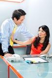 由上司的性骚扰在亚洲办公室 免版税库存图片