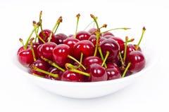 由上面决定的白色盘用红色成熟樱桃填装了 免版税库存图片