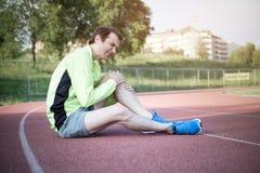 由于受伤的腿的连续运动员感觉痛苦 免版税库存图片
