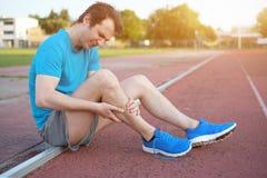 由于受伤的腿的连续运动员感觉痛苦 库存照片