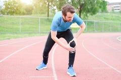 由于受伤的腿的连续运动员感觉痛苦 免版税库存照片
