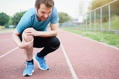 由于受伤的膝盖的连续运动员感觉痛苦 免版税库存图片