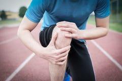 由于受伤的膝盖的连续运动员感觉痛苦 库存图片