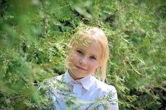 由于叶子,女孩在庭院看  图库摄影