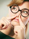 由于恶臭恶臭,女孩捏她的鼻子 免版税库存照片