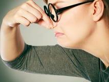 由于恶臭恶臭,女孩捏她的鼻子 免版税图库摄影