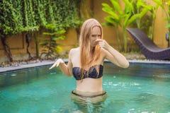 由于水池,充满憎恶的年轻女人在他的面孔少量引导,某事发恶臭,非常在游泳场的难闻的气味 图库摄影