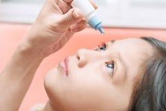 由于眼刺激,照顾申请眼药水于她的女儿 免版税库存照片