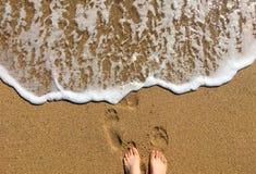 由享受一个晴天的海边的妇女腿 免版税图库摄影