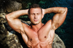 由休息的海的可爱的肌肉年轻人,眼睛关闭了 免版税库存照片