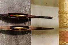由传统木织布机,木短管轴,泰国的编织的金黄丝绸 库存图片