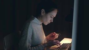 由信用卡的女性买的网络购物在使用笔记本的家在晚上 股票录像