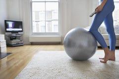 由健身球观看的电视的妇女 免版税库存图片