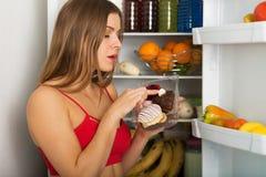 由冰箱的运动的妇女 免版税库存照片