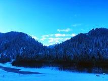 由冻河的村庄冬天日出的 免版税库存照片