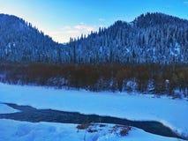 由冻河的村庄冬天日出的 免版税库存图片