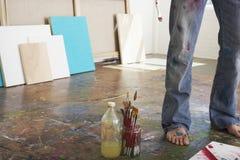 由刷子的艺术家的腿和油漆稀释剂在演播室 免版税库存图片