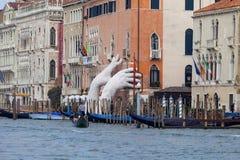 由劳伦斯投入两只巨型手的昆因支持雕塑推出从大运河水,威尼斯,意大利 免版税库存照片