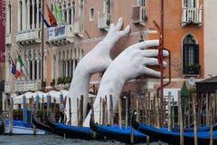 由劳伦斯投入两只巨型手的昆因支持雕塑推出从大运河水,威尼斯,意大利 免版税库存图片