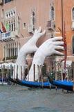 由劳伦斯投入两只巨型手的昆因支持雕塑推出从大运河水,威尼斯,意大利 库存图片