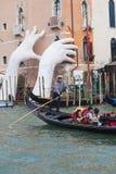 由劳伦斯投入两只巨型手的昆因支持雕塑推出从大运河水,威尼斯,意大利 免版税图库摄影