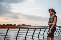 由单独河的行家女孩观看的日落 免版税库存图片