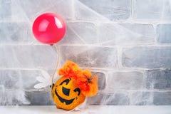 由南瓜做的可怕红色头发小丑,拿着红色气球 免版税库存图片