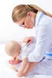 由听诊器的少妇治疗师听的小婴孩心脏 图库摄影