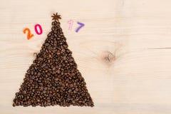 由咖啡豆做的圣诞树在木背景 顶视图,拷贝空间 寒假概念 免版税库存照片