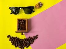 由咖啡豆做的顶视图滑稽的面孔 免版税库存图片