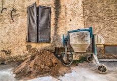 由土气墙壁的水泥搅拌车 库存图片