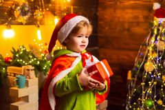 由圣诞树的愉快的小男孩与他的圣诞礼物 小孩穿圣诞老人衣裳 o 库存照片