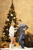 由圣诞树的愉快的年轻夫妇跳舞 免版税图库摄影