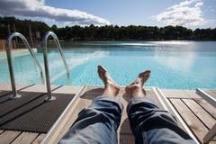 由在他的牛仔裤的水池供以人员放松 库存照片