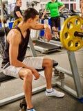 由在体育健身房的杠铃供以人员工作他的身体 免版税库存图片