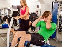 由在体育健身房的杠铃供以人员工作他的身体 库存图片