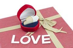 由在红色圆环盒的木头做的心脏标志在有丝带的红色礼物盒做从回收纸 免版税库存图片