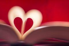 由在红色背景的书页做的模糊的心脏 免版税库存图片