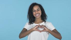 由在蓝色背景隔绝的非洲女孩的手工制造心脏 股票录像