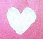 由在闪烁boke柔光的被撕毁的纸做的心脏形状。 免版税库存图片