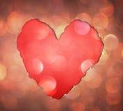 由在闪烁boke柔光的被撕毁的纸做的心脏形状。 库存图片