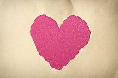 由在闪烁boke柔光的被撕毁的纸做的心脏形状。 免版税库存照片