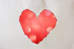 由在闪烁boke柔光的被撕毁的纸做的桃红色心脏形状。 免版税库存图片